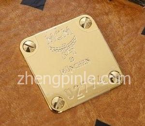 真MCM包铜牌上的塑料保护膜是十字型